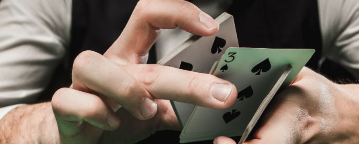 Blackjack Dealer holding a pack of cards with 3 of spades at the bottom