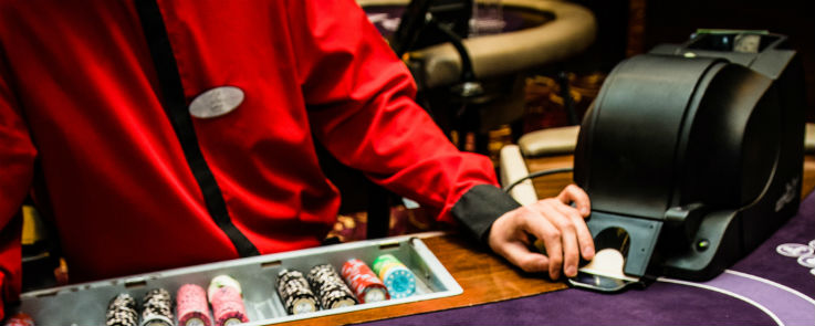 Blackjack Dealer with casino chips and cards shuffle machine